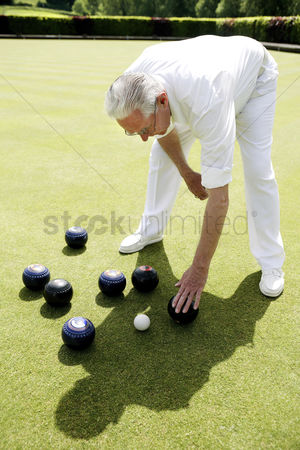 Selection : Man bending down to pick up bowling balls