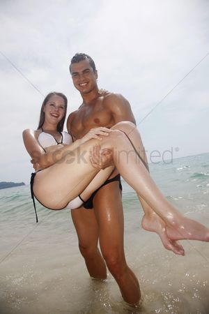 Eastern european ethnicity : Man carrying woman on the beach
