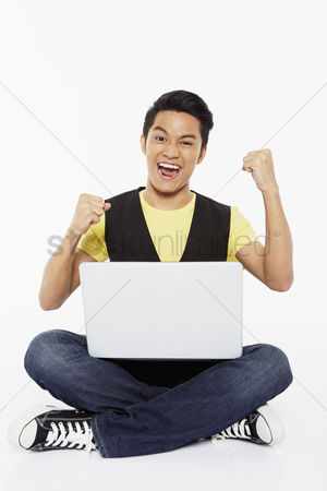Portability : Man cheering while using laptop