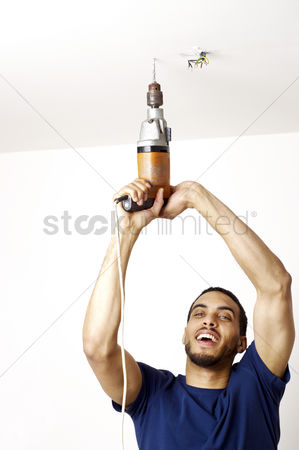 Careful : Man drilling the ceiling