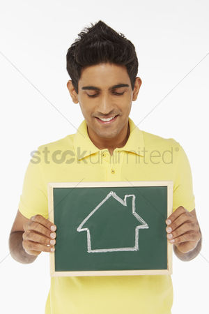 Malaysian indian : Man holding a blackboard with a house doodle on it