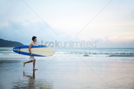 Strong : Man holding a surfboard while running on the beach