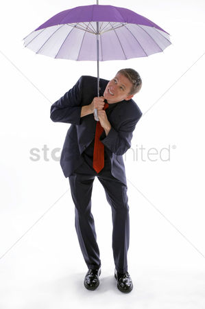 Accessories : Man in business suit holding an umbrella while checking the weather