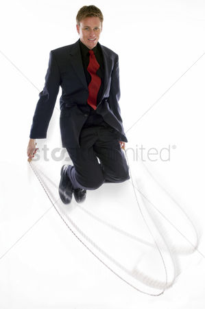 Strong : Man in business suit playing with skipping rope