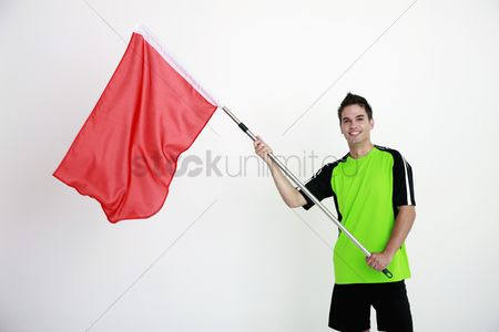 Flag : Man in football jersey holding a red flag