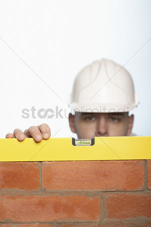 Careful : Man in hard hat using level to check brick wall high section