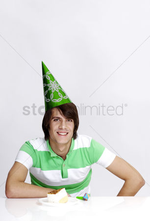 Composed : Man in party hat with cake on the table