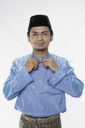 Baju melayu : Man in traditional clothing buttoning his blouse