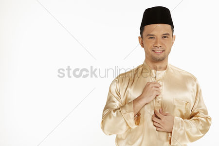 Baju melayu : Man in traditional clothing buttoning up his blouse