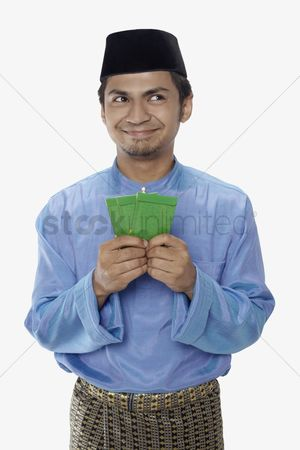 Baju melayu : Man in traditional clothing holding green packets