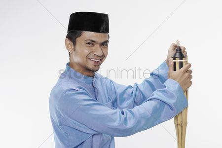 Baju melayu : Man in traditional clothing lighting up oil lamp