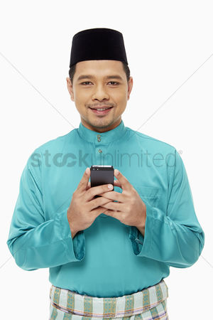 Baju melayu : Man in traditional clothing sending a text message