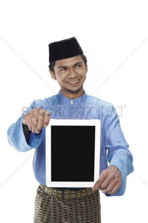 Baju melayu : Man in traditional clothing showing digital tablet