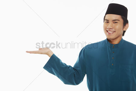Baju melayu : Man in traditional clothing showing hand gesture