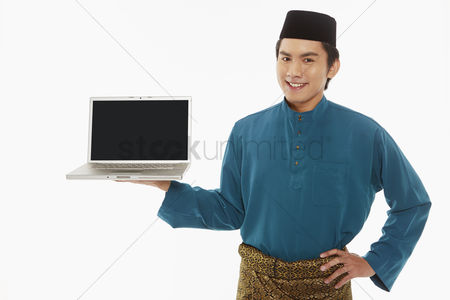 Traditional clothing : Man in traditional clothing showing laptop