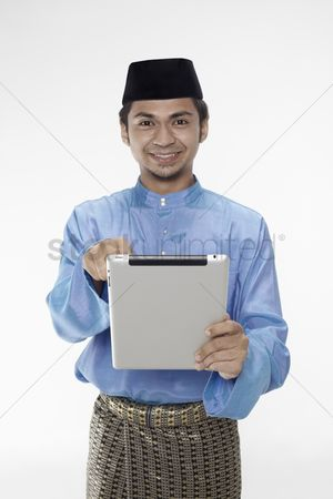 Baju melayu : Man in traditional clothing using digital tablet