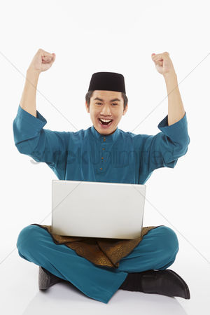 Baju melayu : Man in traditional clothing using laptop and cheering