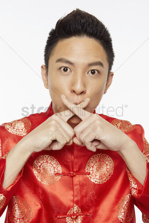 Lunar new year : Man in traditional clothing with fingers against his lips