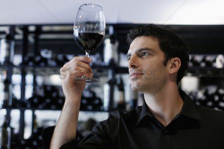 Elegance : Man inspecting a glass of red wine