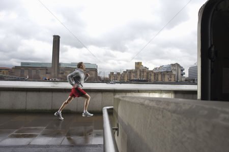 Fitness : Man joggin along the thames with the tate modern in the background