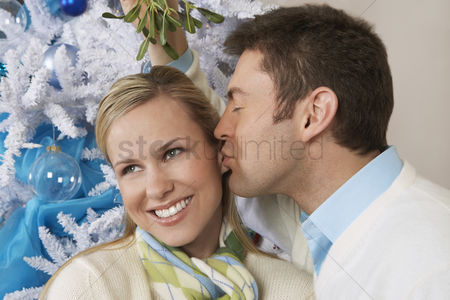 Kissing : Man kissing woman under mistletoe