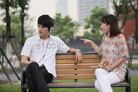 Ignorance : Man listening to music on the headphones  woman scolding man