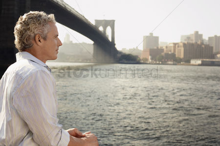 Mid adult man : Man looking at river by brooklyn bridge