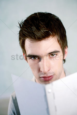 Composed : Man looking at the camera while reading