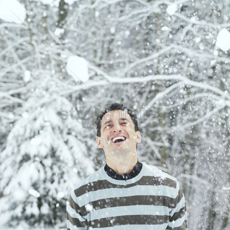 Winter : Man looking up smiling with snow dropping on his face