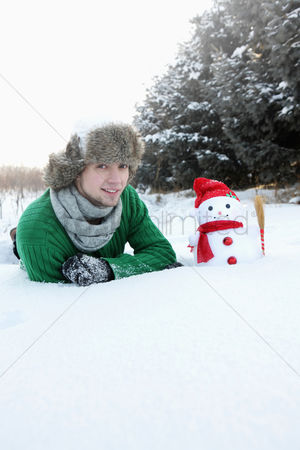 Cold temperature : Man lying on snow with snowman