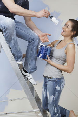 Paint brush : Man on ladder trying to paint woman