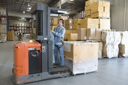 Truck : Man operating fork lift truck in distribution warehouse