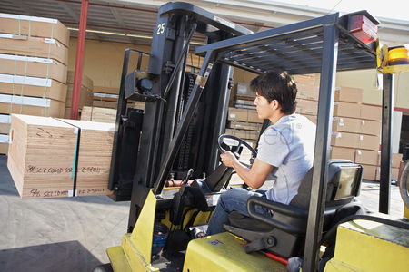 Forklift : Man operating forklift outside rear view