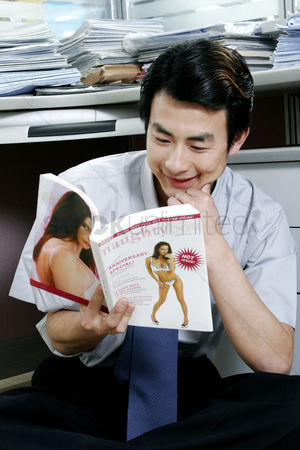 Amazed : Man reading pornographic magazine in the office