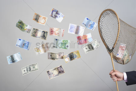 Business suit : Man s hand holding butterfly net catching flying banknotes