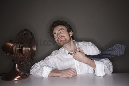 China : Man sitting beside electric fan