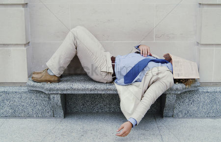Rest : Man sleeping on the bench with newspaper covering his face