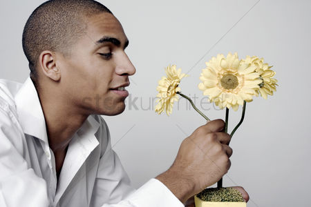 Enjoying : Man smelling the scent of flowers