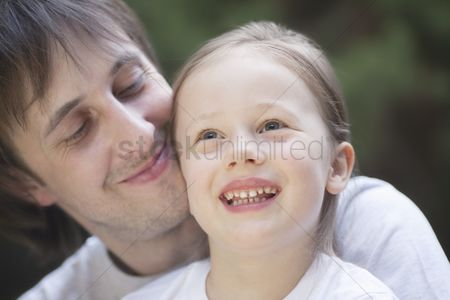 Proud : Man smiles proudly holding girl on his knee