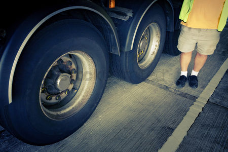 Supervisor : Man standing next to truck wheels