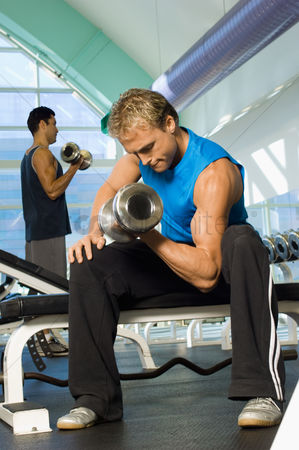 Dumbbell : Man using dumbbell in gymnasium