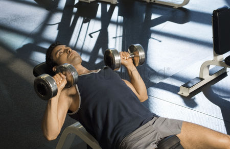 Dumbbell : Man using dumbbells in gymnasium