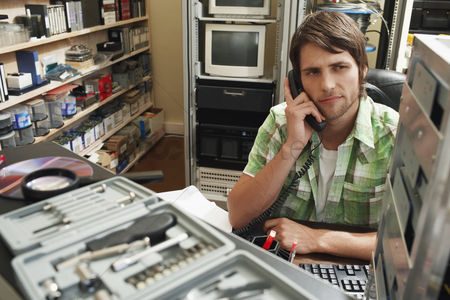 Office worker : Man using phone surrounded by computer equipment