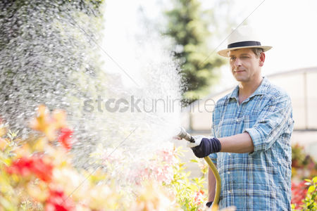 Greenhouse : Man watering plants outside greenhouse