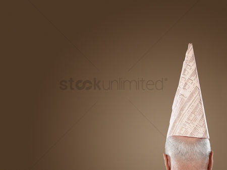 Ignorance : Man wearing dunce hat high section back view