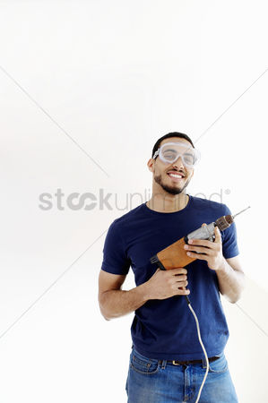 Strong : Man with goggles holding a drill