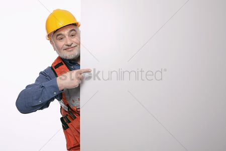 Finger : Man with hardhat pointing at a placard