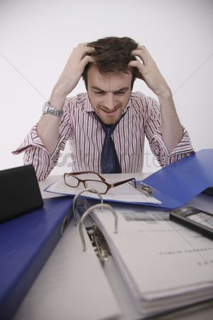 Frowning : Man with head in hands looking at files on the table