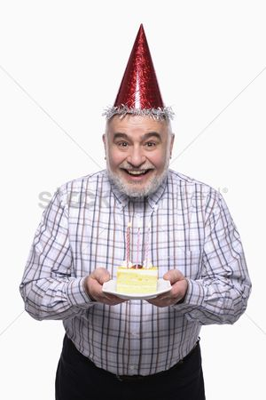 Celebrating : Man with party hat holding a plate of birthday cake