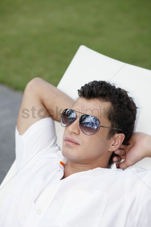 Eastern european ethnicity : Man with sunglasses relaxing on lounge chair